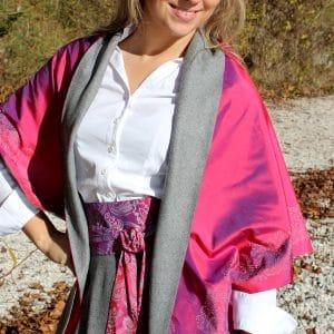 Trachtenmode für Damen: grauer Trachtenrock mit weißer Bluse dazu das kräftig leuchtende Dreieckstuch in der Farbe Pink