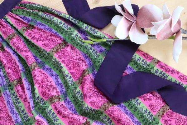 DIrndlschürze mit handbedrucktem Blumenmuster und lilafarbenen Seidenbändern