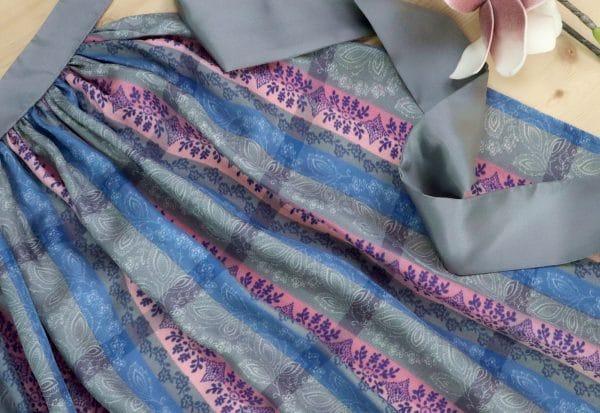 Elegante Dirndlschürze in Grau und Blautönen, handbedruckt